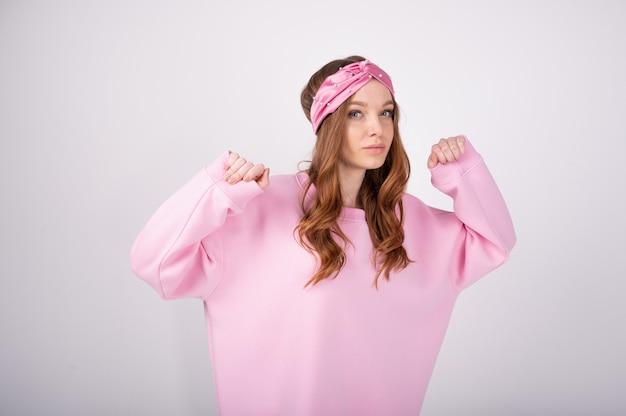 Taille-up shot van aantrekkelijke jonge vrouw met rood haar, gekleed in casual roze losse sweatshirt