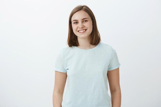 Taille-up shot van ambitieuze vrolijke en schattige vrouwelijke brunette in trendy t-shirt glimlachend vreugdevol verheugd en tevreden terwijl felicitaties ontvangen voor het winnen van prijs over witte muur