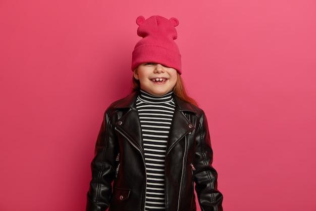 Taille-up shot van blij mooi meisje lacht vreugdevol, verbergt gezicht met roze hoed, gekleed in leren jas, breed lacht, heeft witte tanden, geïsoleerd op roze muur, verheugt zich iets. klein kind binnen