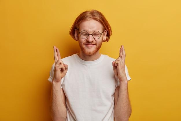 Taille-up shot van blije roodharige man heeft wens om voor een droombaan te worden gesolliciteerd