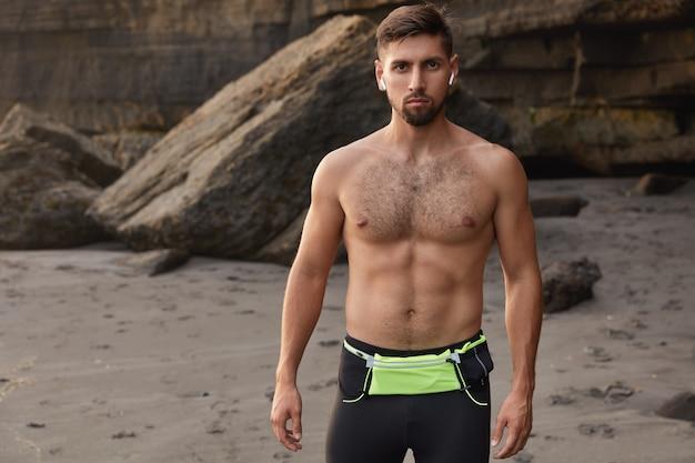 Taille-up shot van bodybuilder die in goede fysieke conditie is, ziet er direct uit