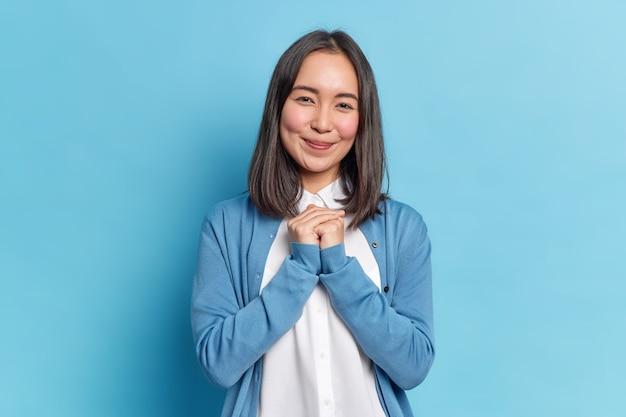 Taille-up shot van brunette jonge aziatische vrouw houdt handen bij elkaar, stelt zich voor dat iets met een blije uitdrukking een casual trui draagt en een tevreden uitdrukking heeft