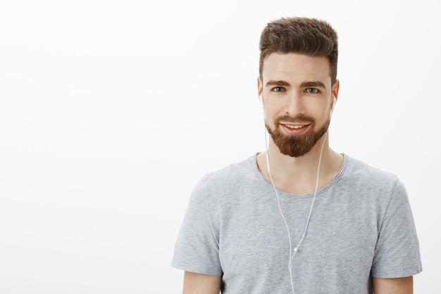 Taille-up shot van charismatische knappe volwassen man met baard en blauwe ogen glimlachend blij en gedurfd oordopjes dragen die de juiste stemming zoeken naar creatieve ideeën terwijl hij naar muziek luistert over een grijze muur