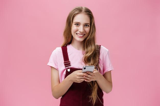 Taille-up shot van charmante aangename jonge vrouw met golvend natuurlijk blond haar in corduroy overall met smartphone starend naar de camera opgetogen en gelukkig bellende vriend, poserend over roze achtergrond.