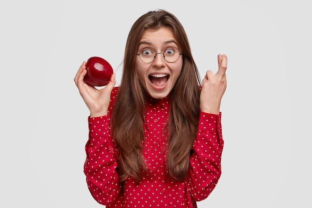 Taille-up shot van dolblij dame houdt vingers gekruist, bidt voor geluk, houdt verse appel vast, geniet van gezonde voeding, gekleed in rode kleding