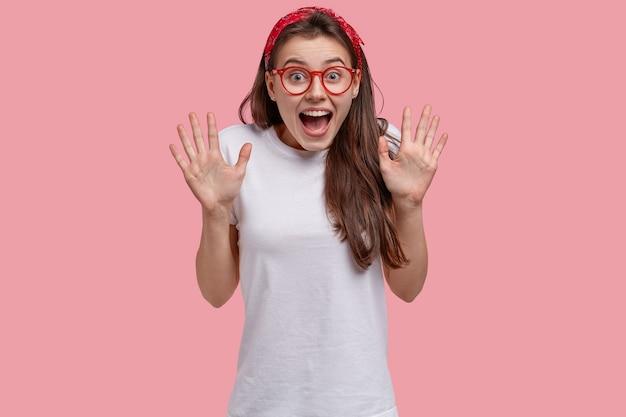 Taille-up shot van dolgelukkig aantrekkelijke vrouw toont palmen, roept positief, draagt een bril en een wit t-shirt