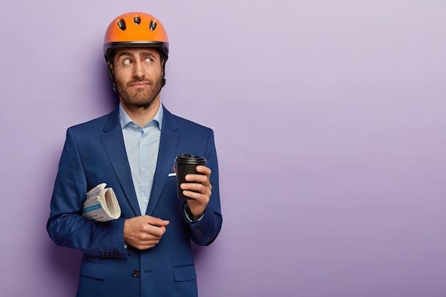 Taille-up shot van doordachte zakenman poseren in stijlvol pak en rode helm op kantoor