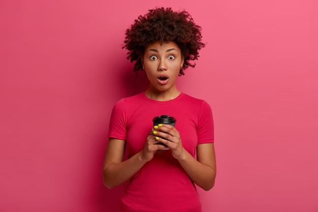 Taille-up shot van emotionele stomverbaasde vrouw staart met afgeluisterde ogen, drinkt koffie om te gaan, realiseert schokkend nieuws tijdens het praten met vriend, geniet van warme drank, poseert tegen roze muur