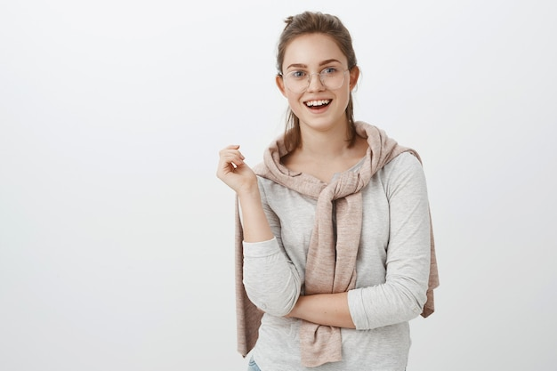 Taille-up shot van geamuseerde sociale goed uitziende europese vrouw met gekamd haar in bril en trui vastgebonden over nek gebaren tijdens gesprek en glimlachend breed geïnteresseerd in gesprek