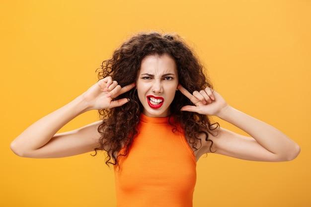 Taille-up shot van geïrriteerde, gehinderde stijlvolle vrouw met krullend haar en rode lippenstift die samenknijpende tanden op elkaar houdt, wachtend op een luide knal die oren bedekt met wijsvingers die geïrriteerd zijn door luidruchtige buren.