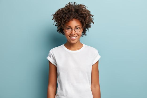 Taille-up shot van gelukkig gekrulde vrouw met brede glimlach, optische bril en casual effen wit t-shirt draagt, goede emoties uitdrukt, geniet van een mooie dag, geïsoleerd op blauwe achtergrond. gezichtsuitdrukkingen