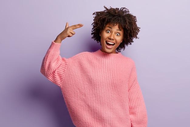 Taille-up shot van gelukkig grappig afro-amerikaans meisje schiet in de tempel, heeft plezier binnen, maakt vingerpistoolgebaar, draagt een oversized roze trui, kantelt het hoofd tegen de paarse muur. kijk, ik pleeg zelfmoord