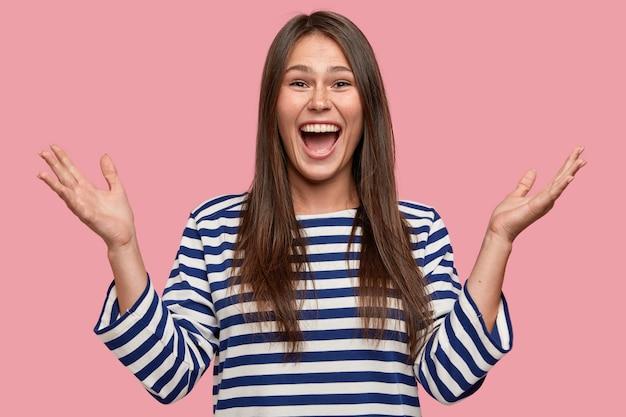 Taille-up shot van gelukkig meisje met sproeten huid, werpt handen, gebaren positief, schreeuwt van vreugde, blij