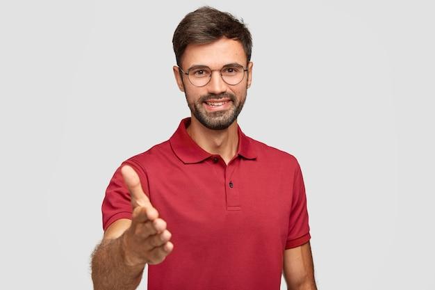 Taille-up shot van gelukkig ongeschoren man geeft handdruk, begroet met iemand, glimlacht oprecht