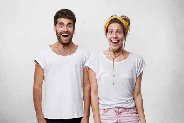 Taille-up shot van gelukkige opgewonden man en vrouw gekleed in witte t-shirts die verbaasd en opgewonden kijken met open mond, verheugend op succes, overwinning, prestatie of goed nieuws