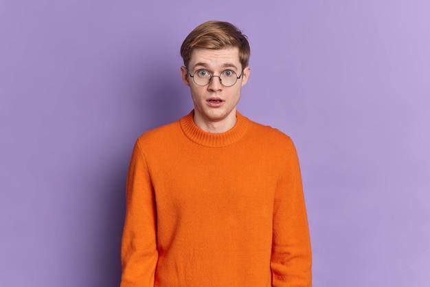 Taille-up shot van geschokte europese man houdt mond open houdt de adem in van verbazing hoort ongelooflijk nieuws draagt ronde bril en oranje trui