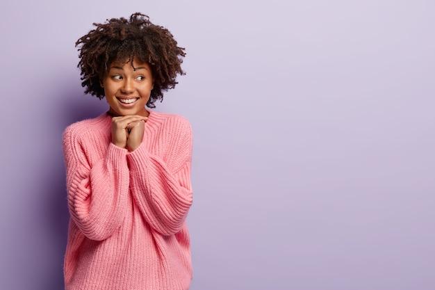 Taille-up shot van goed uitziende lachende tienermeisje houdt beide handen samen onder de kin, gefocust weg, voelt verlegen, krijgt compliment van vreemdeling, kijkt met opgetogen uitdrukking. menselijke emoties
