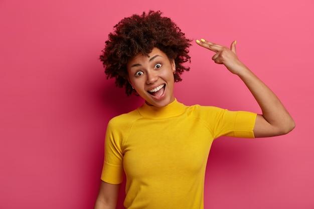 Taille-up shot van grappige afro-amerikaanse vrouw maakt vingerpistool pistool in tempel, kantelt hoofd, lacht positief, draagt gele t-shirt, doet alsof schieten en zelfmoord pleegt, geïsoleerd op roze muur