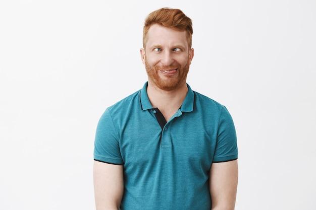 Taille-up shot van grappige emotionele en speelse onvolwassen europese man met rood haar, met loensen en rollende ogen opzij, tong uitsteken, dollen en aping, met hilarische gezichten