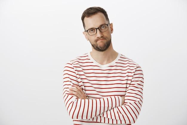 Taille-up shot van intens pissige europese ondernemer in zwarte bril, handen op de borst kruisen en lippen op elkaar klemmen