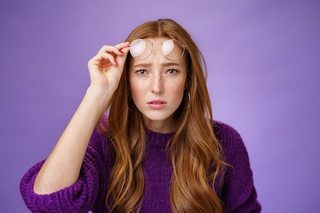 Taille-up shot van intens verwarde en onzekere schattige roodharige vrouw kan niet kijken zonder een bril met slecht zicht, een bril afzetten en naar de camera loensen onzeker, niet in staat om over de paarse muur te lezen.