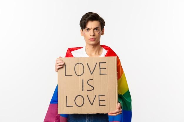 Taille-up shot van jonge lgbtq mannelijke activist, die een regenboogvlag draagt en liefde vasthoudt, is liefdeskaartteken voor pride-parade, vechtend voor mensenrechten, wit.