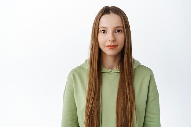 Taille-up shot van jonge mooie vrouw met lang gezond haar, natuurlijke naakt make-up, glimlachend en vastberaden kijken naar voren, staande in hoodie tegen witte muur
