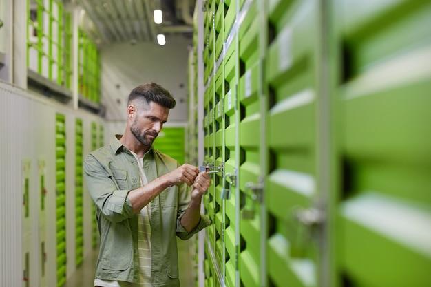 Taille-up shot van knappe bebaarde man opening hangslot op deur van self storage unit, kopie ruimte