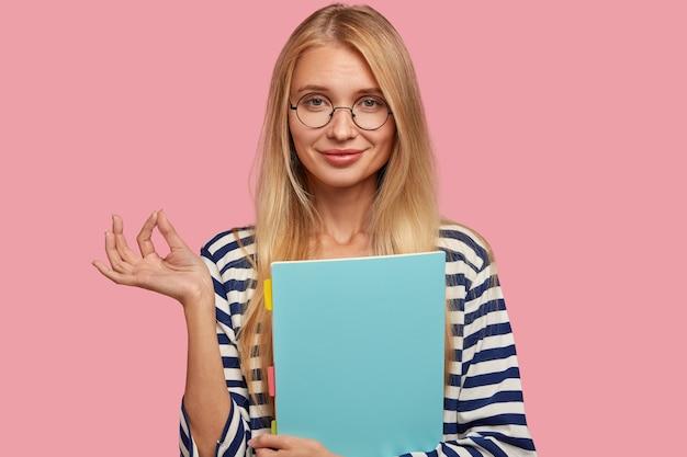 Taille-up shot van knappe blonde vrouw met positieve uitdrukking, toont akkoord gebaar,
