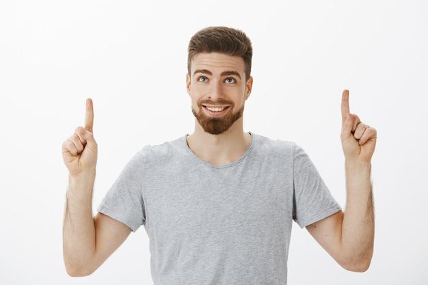 Taille-up shot van knappe mannelijke man met blauwe ogen en baard glimlachend vreugdevol en zelfverzekerd handen omhoog kijkend en wijzend opgetogen en blij staande tevreden over grijze muur