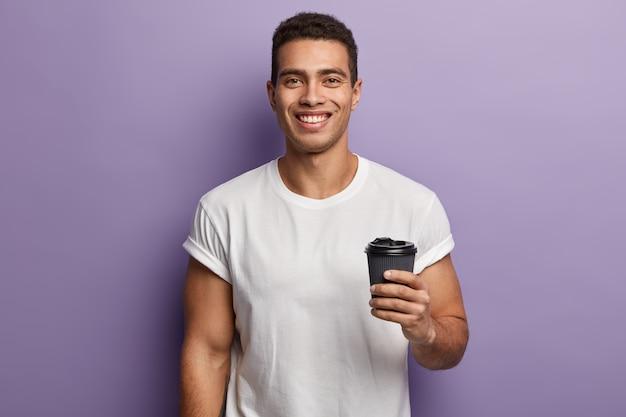 Taille-up shot van lachende vrolijke knappe man houdt papieren afhaalkoffie vast, geniet van vrije tijd met vriend, drinkt aromatische drank, draagt witte mock-up t-shirt, modellen tegen paarse muur