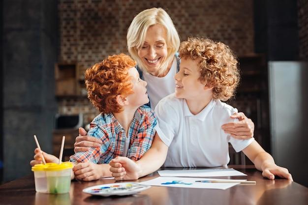 Taille-up shot van liefdevolle bejaarde vrouw knuffelen haar kleinzonen terwijl ze allemaal aan een tafel samenkomen en thuis samen tekenen.