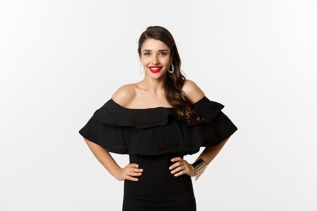 Taille-up shot van mooie vrouw met rode lippenstift, zwarte jurk dragen en glimlachend tevreden, staande op witte achtergrond.