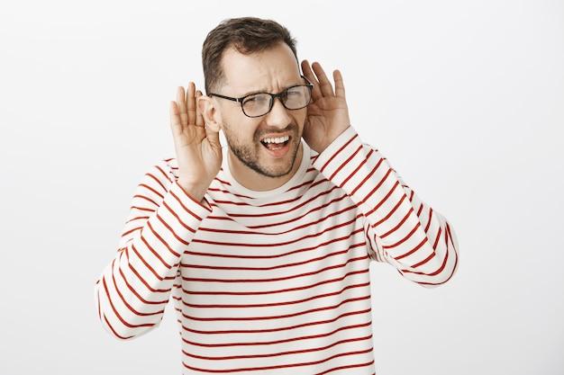 Taille-up shot van ondervraagde verwarde blanke man in zwarte bril