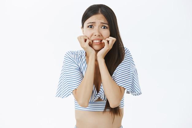 Taille-up shot van onzeker bezorgd en bang onschuldig meisje met donker haar in bijgesneden top dat bibbert van schrik fronsende bijtende vingernagels
