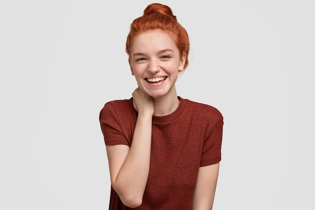 Taille-up shot van positieve roodharige vrouwelijke meisje heeft sproeten huid, glimlacht zachtjes