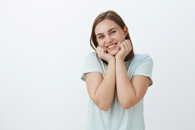 Taille-up shot van schattige en zachte europese vrouw liefdevol leven leunend hoofd schattig op handpalmen en glimlachend vreugdevol gevoel vrolijk en levend poseren geamuseerd tegen grijze muur