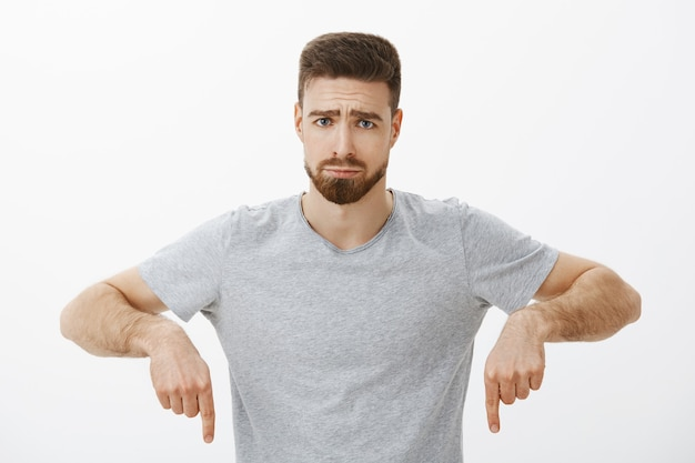 Taille-up shot van sombere, schattige mannelijke vriend met baard en bruin haar, fronsend en pruilend met een dom, ongelukkig gezicht dat naar beneden wijst, zich eenzaam en verdrietig voelen nadat er een oneerlijk iets over de grijze muur is gebeurd