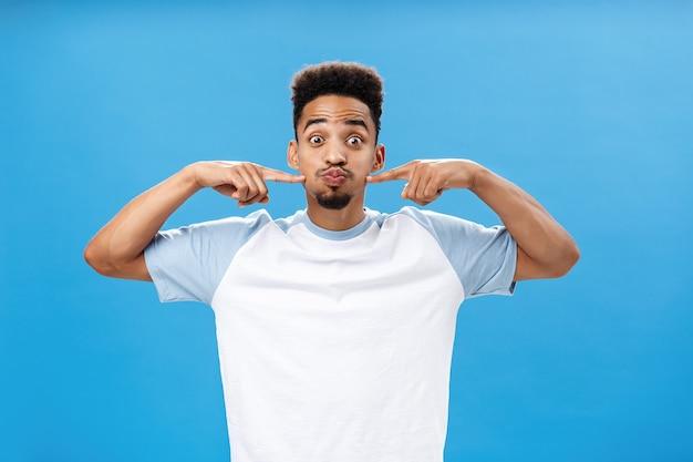 Taille-up shot van speelse, vrolijke, aardige afro-amerikaanse man met tatoeage op handpalm die de adem inhoudt en vrolijk pruilt en naar de wangen prikt met wijsvingers die ogen knallen terwijl hij plezier heeft over blauwe achtergrond