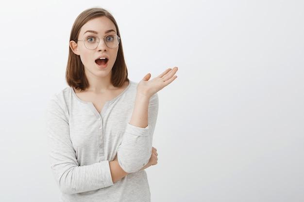 Taille-up shot van spraakzaam vermaakt en geamuseerd goed uitziend slim meisje in bril en blouse met handpalm zwaaien tijdens gesprek staand met geopende mond midden in een interessante discussie