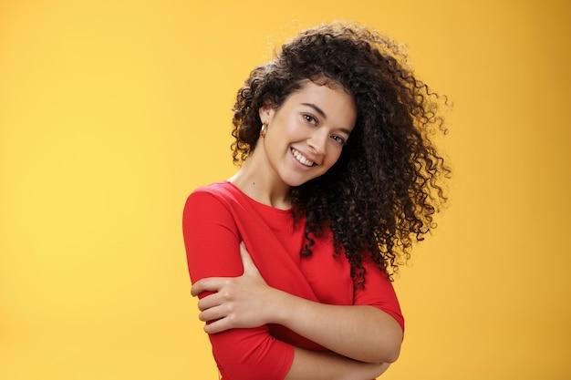 Taille-up shot van tedere vrouwelijke en zachte vrouw met krullend kapsel naar rechts gekamd, hoofd kantelend en flirterig lachend, romantisch starend naar camera die zichzelf omhelst over gele achtergrond.