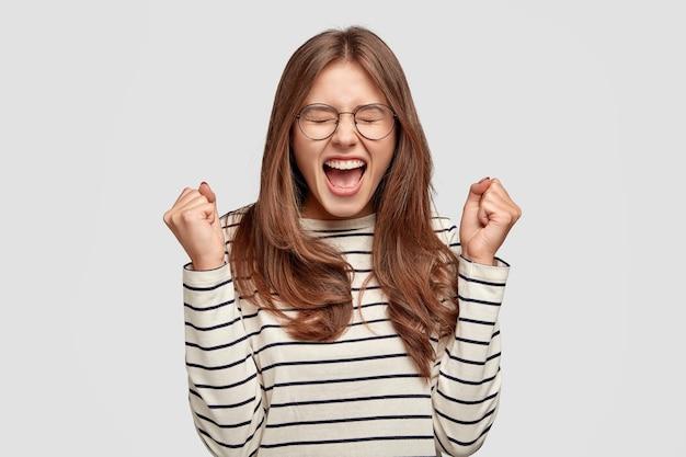 Taille-up shot van tevreden dolblij zelf vastberaden jonge vrouw steekt handen met gebalde vuisten, juicht succes toe