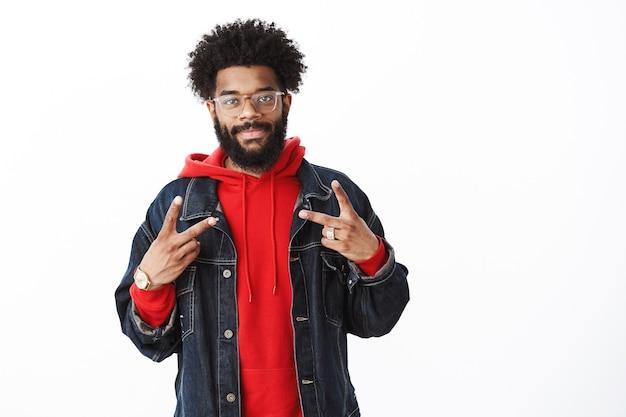 Taille-up shot van tevreden en vriendelijk lachende afro-amerikaanse bebaarde man met afro kapsel in bril, spijkerjasje over rode hoodie grijnzend naar camera en overwinningsteken tonen over grijze muur
