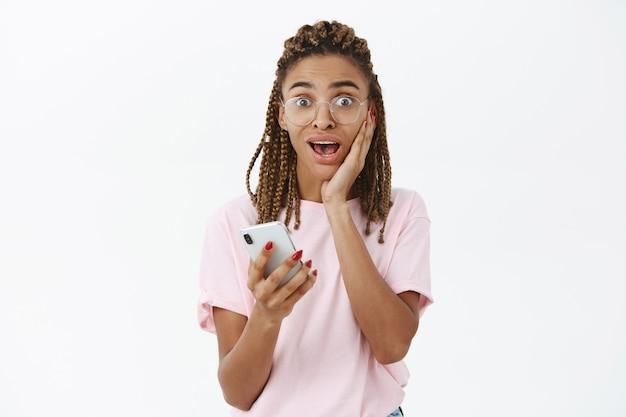 Taille-up shot van verbaasd sprakeloos aantrekkelijk slim donker meisje met dreadlocks die naar adem snakken van blij nieuws