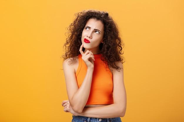 Taille-up shot van verbijsterde, attente en slimme vrouw met krullend kapsel in rode lippenstift en bijgesneden bovenkant in hmm pose, kin aanrakend, fronsend kijkend naar de linkerbovenhoek, vastberaden denken.
