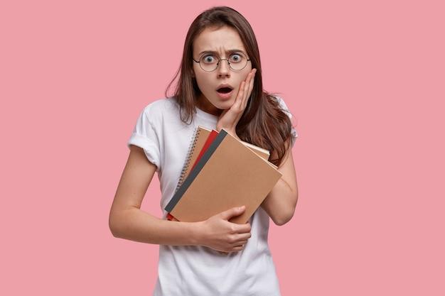 Taille-up shot van verbijsterde blanke vrouw met angstige uitdrukking, opent mond wijd, houdt blocnotes vast, gekleed in wit casual t-shirt