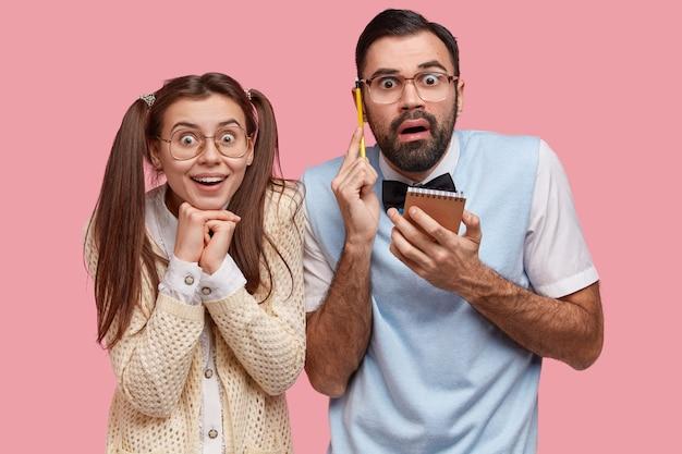 Taille-up shot van verrast emotionele leraar en vrouwelijke stagiair camera staren, samen studeren, records opschrijven in kladblok, naast elkaar staan