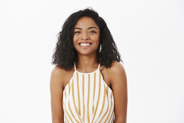 Taille-up shot van vriendelijk ogende charmante en timide afro-amerikaanse vriendin met krullend kapsel