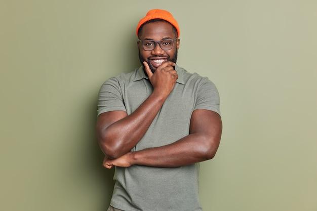 Taille-up shot van vrolijke man houdt kin glimlacht gelukkig in goed humeur kijkt direct naar voorkant heeft positief gesprek met gesprekspartner draagt casual t-shirt en oranje hoed vormt binnen