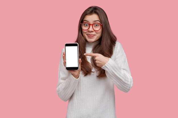 Taille-up shot van vrolijke mooie jonge vrouw met donker haar wijst naar het lege scherm van de mobiele telefoon, toont ruimte voor uw advertentie